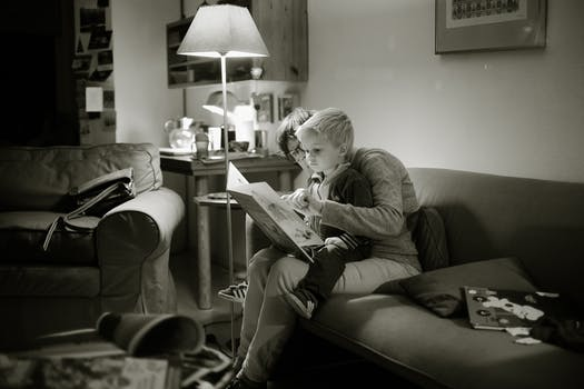 reading to a kid black and white photo | Lift Legal