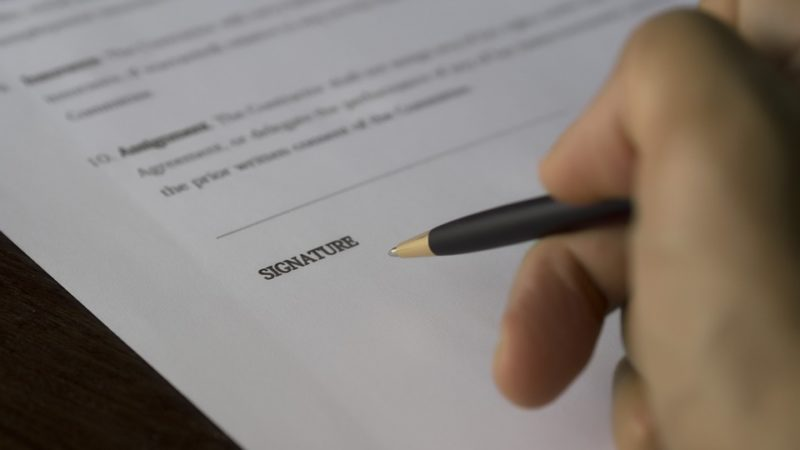 signing paper document | Lift Legal
